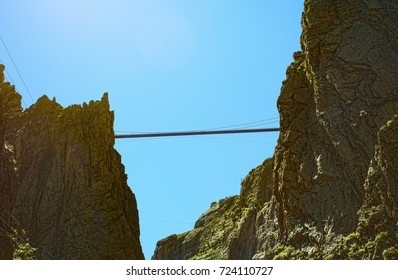 Looking up at from the bottom of the 1250 foot Royal Gorge in Canon Colorado, at pedestrians on the suspension bridge that are crossing it.