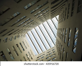 Looking up to the bright light sky through modern quardrilateral ceiling window