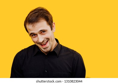 looking at camera with funny flirty face expression while standing on yellow background, copy space, positive emotions and happiness concept, isolated