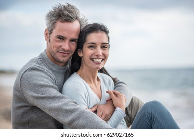 Looking at camera, a middle-aged couple sitting on a rock at the beach. They are wearing sweaters and jean, the man has grey hair