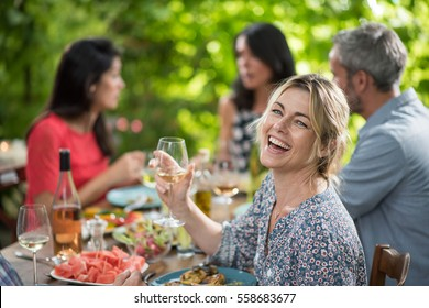 Looking at camera, portrait of a beautiful middle aged blond woman sharing a meal friends on a terrace table in summer, she has a glass of wine at hand