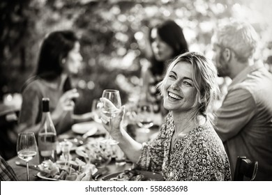 Looking at camera, portrait of a beautiful middle aged blond woman sharing a meal friends on a terrace table in summer, she has a glass of wine at hand. Black and white