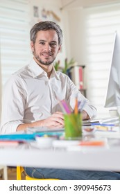Looking at camera. Portrait of a grey haired businessman wearing beard at office, he works on a computer in an creative agency