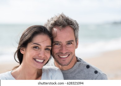 Looking at camera. Portrait of a middle-aged couple having fun on the beach, they are wearing sweaters and the man has gray hair