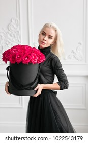 looking at the camera. Young pretty girl with cute face and long blond hair. Woman standing and holding black box with pink roses. Fashion style studio portrait. Luxury interior