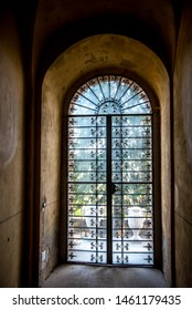 Looking from castle into back garden through wrought iron gate towards marble urns