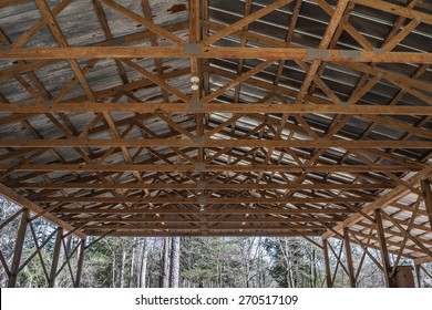 Looking up at the ceiling joists and rafters of an open wall building.