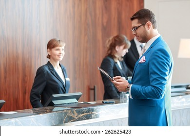 Looking for check-in information. Young handsome businessman in classical blue suit looks at his tablet device standing just in front of the hotel reception desk where young receptionists welcomes him