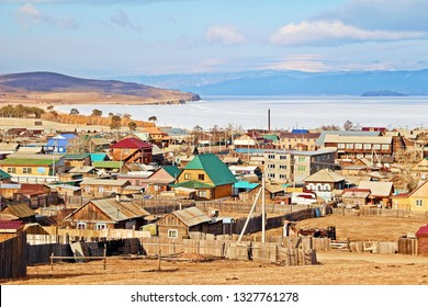 Looking at colorful roof of houses in Khuzhir city on Olkhon island in front of icy lake in late winter