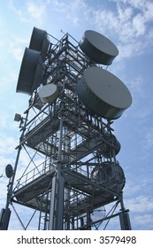 Looking up at communication tower with numerous microwave dishes