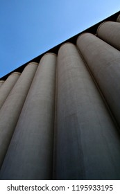 Looking up at concrete or cement storage silos at an industrial flour mill.
