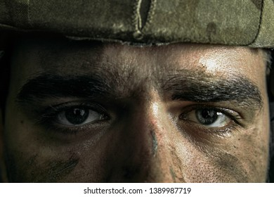 Looking deeper for a reason. Close up portrait of young male soldier. Man in military uniform on the war. Depressed and having problems with mental health and emotions, PTSD, rehabilitation.