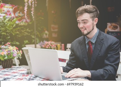 Looking for direction and inspiration, Portrait of happy young businessman sitting with laptop at coffee shop