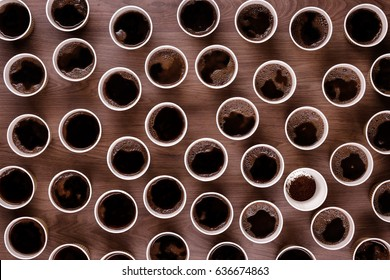 Looking down from above at lots of take away coffee cups on a wooden background all have black coffee in them except one which has coffee granules in it