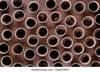 Looking down from above at lots of take away coffee cups on a wooden background all have black coffee in them