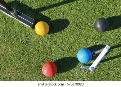 Looking down from above on a game of croquet with a croquet mallet about to strike the yellow ball with the blue ball in the jaws of the steel croquet hoop with the black and red balls nearby.
