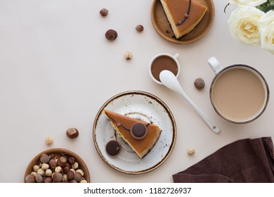 Looking down from above onto a white, wooden table top with a feminine breakfast of cake and coffee along with  flowers  with inspirational quotes.