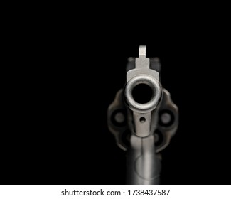 Looking down barrel of handgun, revolver, pointed toward you. Isolated on black background. Concept of crime, violence, shooting, firearm control and safety