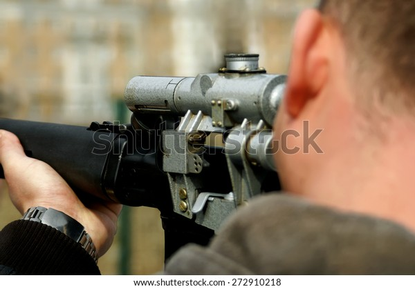 Looking down the barrel of a russian sniper rifle being held by a non identifiable man dressed in casual wear