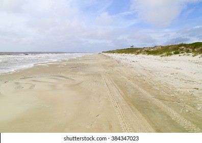 Looking down the beach on Jekyll Island with the surge of waves to the left and the sand dunes to the right.