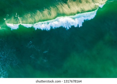 Looking down at beautiful crushing green ocean wave at sunset. Aerial view with copy space.