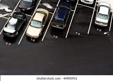 Looking down at cars parked in a parking lot during the winter