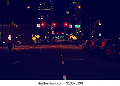 looking down the center of a dark city street with limited human and vehicle traffic with a toned instagram filter