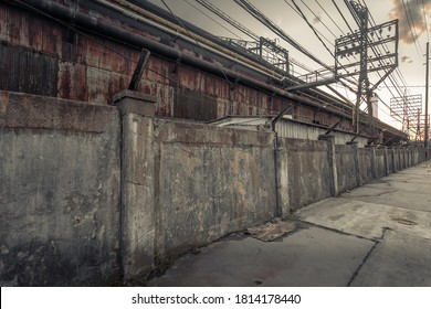 Looking down decrepit old wall in front of abandoned factory with telephone wires in the blue collar midwest