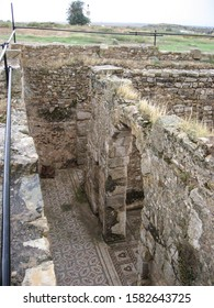 Looking down at an excavation at Bulla Regia, of a home with walls and mosaic floors still intact.