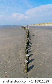 Looking down a gently curved row of wooden posts on West Wittering beach at low tide.