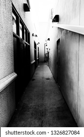 Looking down into a dark creepy alley between buildings, black and white image.