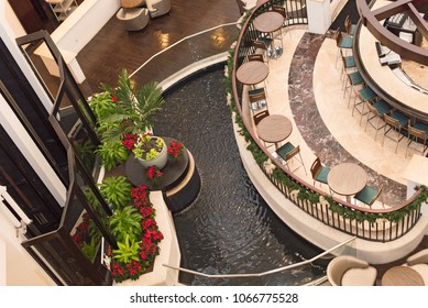 Looking down into hotel bar area with water feature, table and chairs