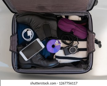 Looking down into an open suitcase in a white bathtub (to prevent bringing bed bugs home from a hotel) with white phone and charger, purple pill minder and eye mask, and black boots and camera
