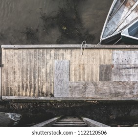 Looking down a ladder to a wooden dock with rowboats.