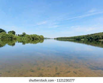 Looking down the length of Staunton Harold Reservoir, in Derbyshire, the blue summer sky and surrounding trees reflected in the calm water.
