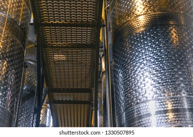 Looking down the line of metal fermenters in a whiskey distillery.