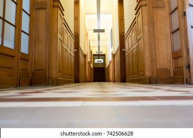 Looking down a long hallway with fluorescent lights at a University in Belgium. Low perspective of a long hallway of a building, warm brown tones.