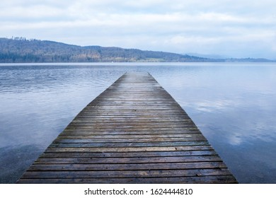 Looking down a long wooden jetty with a diminishing persepective, jutting straight out over a clear calm blue lake relecting the white and blue of the sky, Lake Windermere, cumbria, England, UK