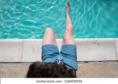 Looking down at man sitting on the edge of the pool with one foot in the water wearing blue swimming trunks. Fit man sits poolside. Caucasian man by an outdoor swimming pool in the summer.