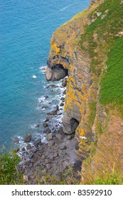 Looking down to the ocean over rocky cliffs to a small bay and two sea caves