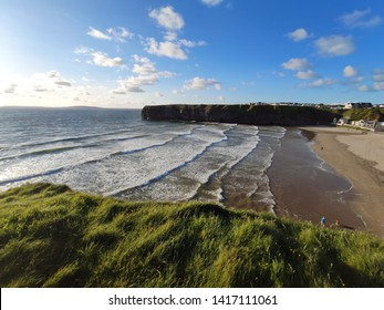 Looking down at the ocean waves and beach from coastal cliffs, Scenic Atlantic coastal town of Ballybunion on the wild Atlantic way, Counry Kerry, Ireland