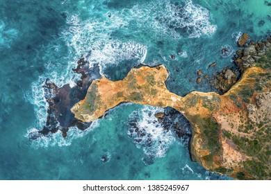 Looking down at ocean waves breaking over eroded rocks - aerial view
