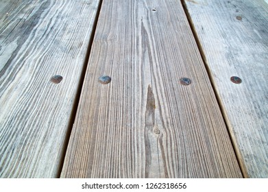 Looking down at old weathered wooden picnic table top.