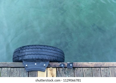 Looking down on a black tyre nailed to a jetty and blue/green water