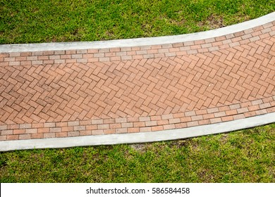 Looking down on a brick walkway through grass