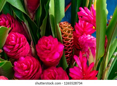 Looking down on a bunch of fresh tropical flowers, vivid pink ginger and green leaves, ready for sale at a farmers market on Kauai.