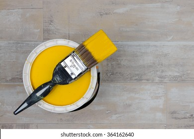 Looking down on a can of Bright Yellow Paint with a loaded brush stood on a shabby style wood floor