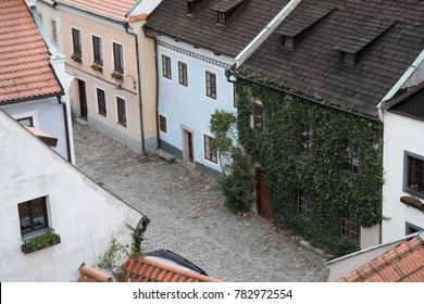 Looking down on a cobblestone street and quaint vernacular houses of the charming medieval town of Cesky Krumlov, Czech Republic. Looking down on streets from above. Ivy growing on side of old house.