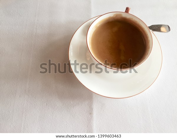 Looking down on a cup of hot coffee on a white tablecloth.