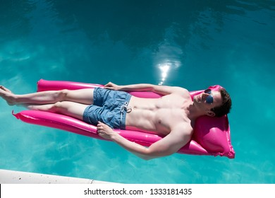 Looking down on fit young white man with ripped abs laying on a pink raft in an outdoor swimming pool wearing aviator sunglasses and blue swimming trunks on a bright sunny day.